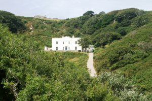 Millcombe House on Lundy. A large white house in the classical style with banks of windows nestles in a wooded green hillside.
